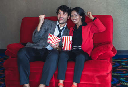 Happy Diverse couple eating popcorn while watching movie at the cinema in movie theater. Handsome caucasian man and black woman in spending time together in Holiday. Entertainment ,enjoyment concept. Imagens