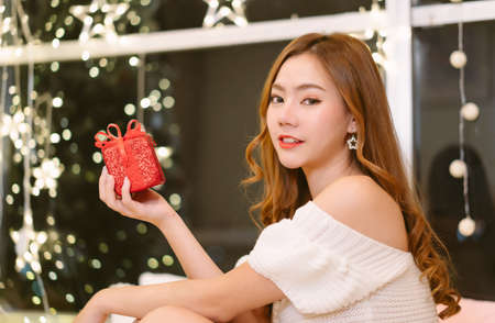 Young beautiful Asian woman wearing knitted warm sweater sit on the floor holding gift box and looking at camera in living room on christmas background at home.Celebrating Christmas,New Year concept . Banco de Imagens