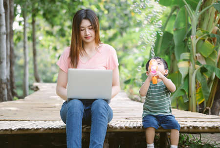 Portrait of young Asian mother and little son sit together on the floor in garden while mom working remotely on laptop and son playing with soap bubbles machine. Childcare and work concept.
