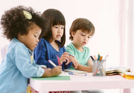 Group of diversity kids drawing and painting with crayon together with fun in art class at the kindergarten. Preschool international, education concept.