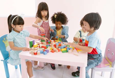 Group of diversity kids playing with colorful blocks on table in class at the kindergarten.Kindergarten international school, education concept.