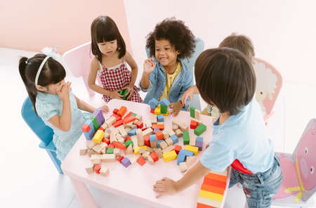Ethnicity diversity group of kids playing with colorful blocks on table in class at the kindergarten. Kindergarten international school education concept. Top view.