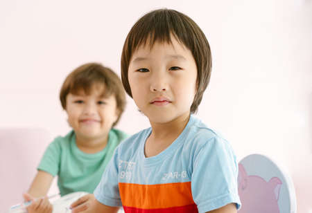 Cute little Asian boy drawing art lesson and looking at camera while his friend smile at camera in international preschool.