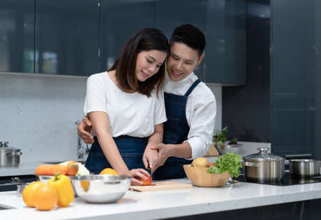Portrait of Asian couple in love standing close together, cuddling and caringly, cooking at kitchen table. Couple spending time together at home. 免版税图像