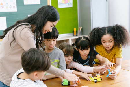 Group of Diverse Elementary School Pupils and Female Asian teacher demonstrating making electric remote control car in science lesson. Education, elementary school, learning, science workshop concept.