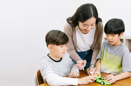 Group of Elementary happy kids and Asian female teacher making electronic toys with colorful in science lesson class. Education, elementary school, learning, science workshop concept. Copy space 免版税图像