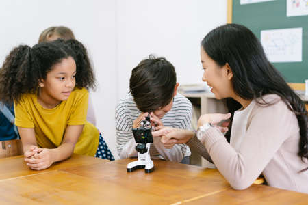 Attentive elementary schoolboy and Asian female teacher with microscopes in science classroom at school with friends. Education, elementary school, learning, science workshop concept.