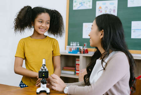 Cute Little African Girl looking and smile with Asian female teacher study microscopes in science classroom at school. Education, elementary school, learning, science workshop concept.
