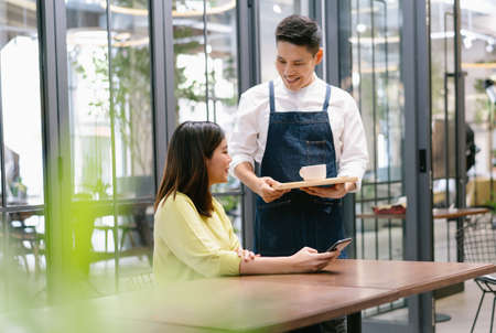 Smiling young Asian waiter serving hot coffee to a female customer. Start up small business owner Concept. 免版税图像