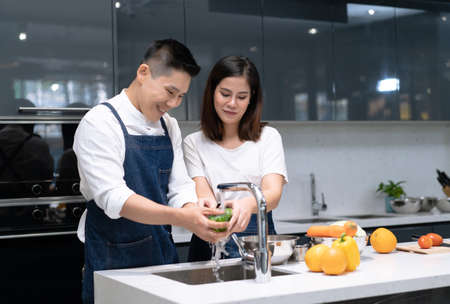 Portrait of young Asian couple in love while washing vegetables for cooking in kitchen at home. Couple spending time together at home. 免版税图像
