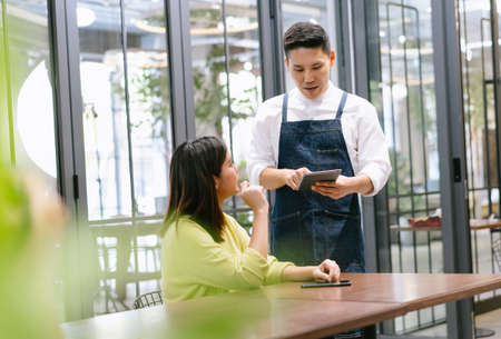 Smiling young Asian waiter using digital tablet to take an order from a customer in a cafe. Technologies helping in business and daily work. Startup small business owner and Service mind concept.