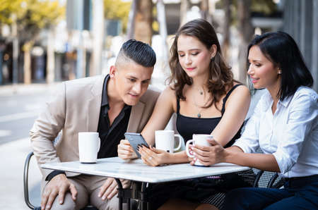 Group of young business people sitting at city street cafe talking and enjoying. They are discussing something on a smart phone.