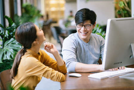 Two Asian collegues sitting at desk talking relaxed behind pc computer in modern office. Informal conversation during break at workplace.
