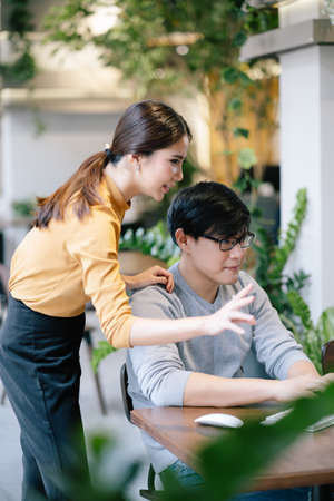 Two Asian creative collegues in smart casualwear discussing new ideas using pc computer in modren office, co-working space. Teamwork Concept. 免版税图像