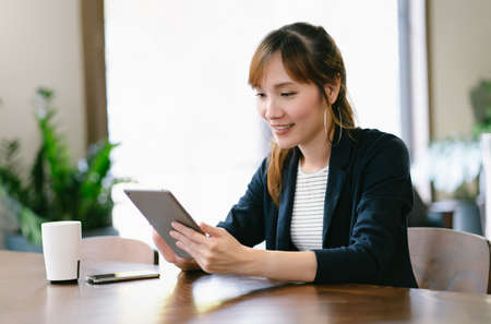 Portrait of young Asian freelancer woman using digital computer tablet, chatting with friends in social network sitting at table in co-working office. Freelance Work, Business People Concept