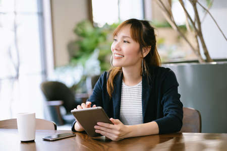 Happy beautiful Young Asian business woman holding digital tablet and looking away while sitting at table in co-working office. Freelance Work, smiling, positive emotion, Business People Concept 免版税图像
