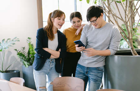 Group of creative young Asian people talking and looking at smart phone while  take break distracted from work in the creative co-working space. Office life, Teamwork, friendship concept 免版税图像