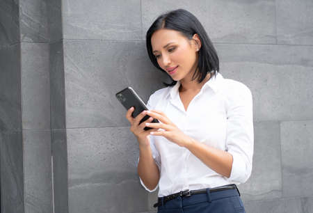 Portrait of young businesswoman using her smartphone, chatting on social media standing outdoor near office. Foto de archivo