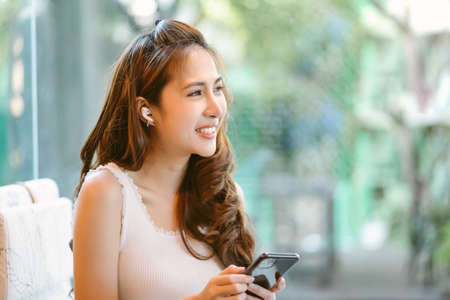 Happy beautiful young Asian woman sitting at the cafe using mobile phone and listening music with earphones. People lifestyle,Music Lover,Weekend Relaxation Concept. 免版税图像