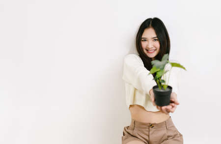 Young beautiful Asian woman smiling friendly holding flower pot on a isolated white background.
