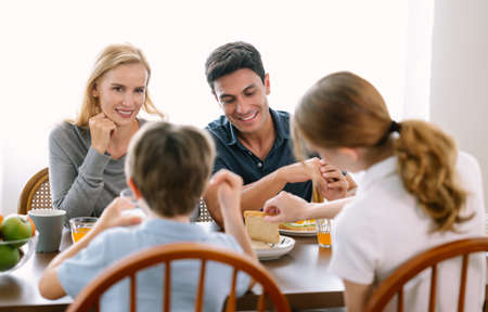 Happy caucasian family with teenage daughter and son smiling and talking while having breakfast in modern kitchen. Family,healthy,fun and lifestyle concept.