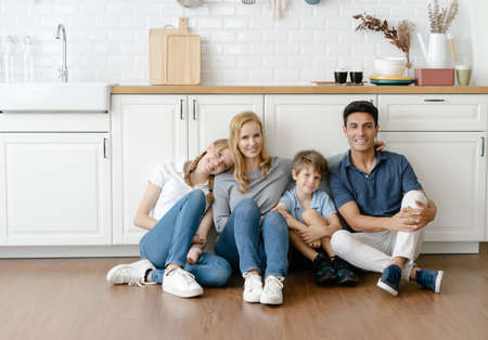 Portrait of Happy Caucasian family with teenage daughter and little son sitting on warm wooden floor in modern kitchen and looking at camera. Family enjoying weekend at home together.