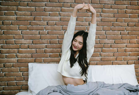 Portrait of young beautiful Asian woman wake up stretching her arms sitting on comfortable bed at brick loft modern style room. She felt very feeling happy and fresh.