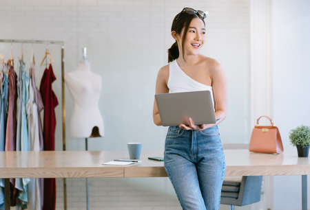 Young beautiful Asian Woman fashion designer working small business using laptop computer and look away dream about good future vision in home office. Startup Small business owner, Freelance work.