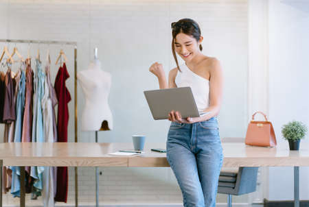 Beautiful young Asian woman fashion designer standing in front of her workplace and holding laptop computer and celebrating success in home office.  Startup Small business owner, Freelance work.