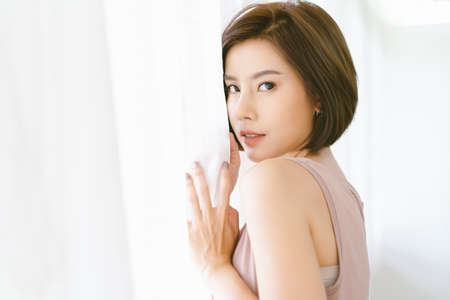 Portrait of beautiful Asian woman opening window white curtains and turning to look and smile at camera. Pretty model girl with perfect fresh clean skin resting at home. Lifestyle and Relax Concept.