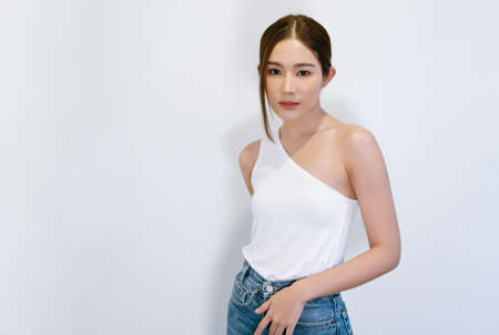 Portrait of fashionable beautiful young Asian woman in stylish strapless with jeans clothes with natural make-up and looking at camera standing near white wall. Lady slim wears white fit clothes.