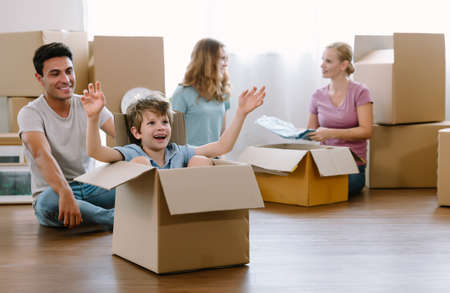 Caucasian father having fun cute little son moving with cardboard boxes and teenage girl with her mother sorted out clothes and collected donations for people in need.Moving to new house or apartment.