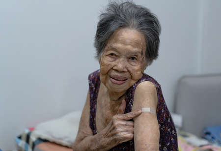 Portrait of Asian grandma showing arm with plaster bandage after vaccination and her doctor. Virus protection. COVID-2019.Caring with older people. Health care Concept.