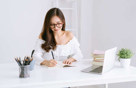 Beautiful young Asian girl sit at desk in living room listening educational on laptop and taking notes at home. Take online course or training at home, education concept.