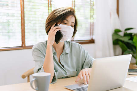 Beautiful Asian Freelancer woman wearing medical mask for protection flu and covid-19. She using laptop computer and talking mobile phone at home during self-isolation and quarantine.Work from home
