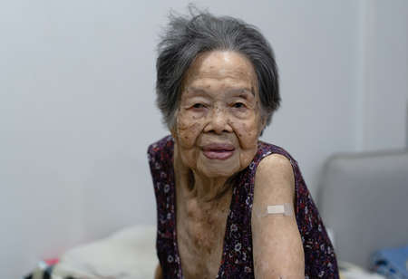 Portrait of Elderly Asain woman showing arm with plaster bandage after vaccination and her doctor. Virus protection. COVID-2019. Health care Concept.