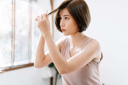 Portrait of beauiful young Asian woman having her hair cut with scissors at home. She's stay at home during the coronavirus pandemic, Self hair care during quarantine.