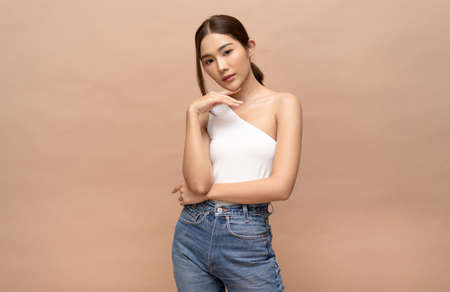 Portrait of fashionable beautiful young sexy Asian woman with natural make-up and looking at camera. Lady slim wears white fit clothes. Girl Posing on a Beige Background. 免版税图像