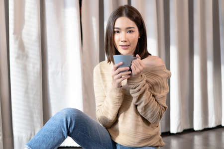 Beautiful young Asian woman wearing a sweater sitting on the floor and holding a coffee or tea at home studio. Happy cheerful relaxing in cold winter and looking at camera. Fashion, Autumn, winter.