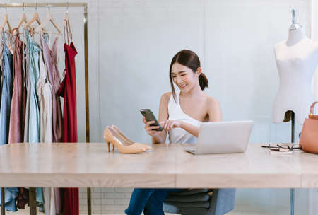Beautiful Female Entrepreneur. Young cheerful Asian woman fashion designer worker online banking smartphone while sitting on desk. Startup Small business owner,Freelance work.  SME marketing concept