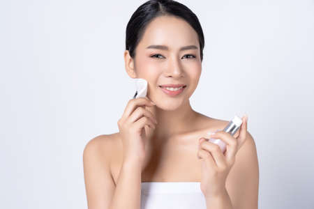 Portait of young beautiful Asian woman removing makeup with cleansing lotion and facial using cotton pads cleaning her face isolated over white background. Perfect Face and Skin Care Concept