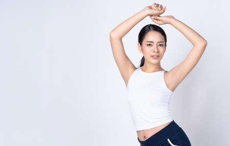 Portrait of beautiful young Asian sports fitness woman posing isolated over white wall background with copyspace for text. Sport And Healthy Lifestyle Banco de Imagens