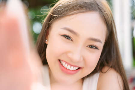 Closeup portrait of inspired caucasian Asian girl with clean skin, natural make-up with broad smile showing her perfect teeth and taking selfie of herself in back yard garden Фото со стока