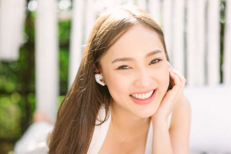Close-up Portrait of smiling young Asian woman touching wireless earbud, listening music in headphone and looking at camera while resting on bench in park. Weekend Relaxation Leisure Concept. Фото со стока