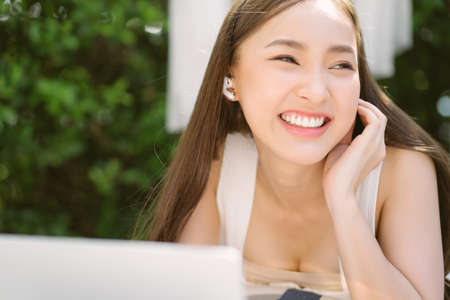 Closeup portrait of beautiful young Asian smilling lying on sofa patio furniture on outdoor patio living room while using laptop and wireless earphone for video call. Holiday and lifestyle concept. Фото со стока