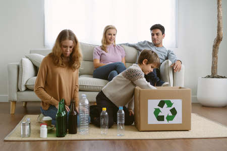 Happy teenage daughter and younger brother sit on the floor  putting empty recycling plastic ,glass bottles into recycle box while parents sit on sofa and look their children in love. Ecology concept.
