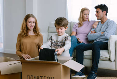 Happy volunteer caucasian family separating donations clothes in carton package donate to needy people in living room at home in winter. Family donating unwanted items. Donation and charity concept.