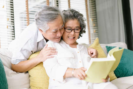 Portrait of beautiful Asian senior couple reading together interesting book while sit on couch in living room at home. Old couple enjoying spending time together concept.