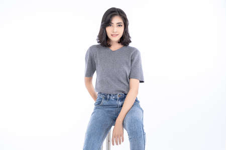 Portrait of beautiful Asian woman in grey t-shirt and jeans with sitting on chair and looking at camera on isolated over white background. People and lifestyle concept.