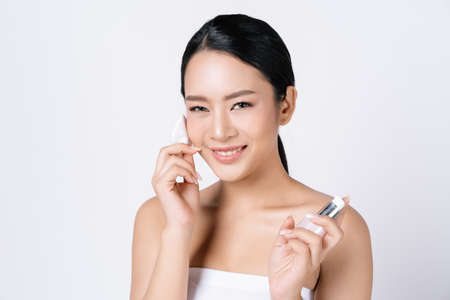 Beautiful young Asian woman applying lotion to cotton disc for cleaning her face and looking at camera isolated over white background. Facial treatment. Cosmetology, Beauty skin care face.